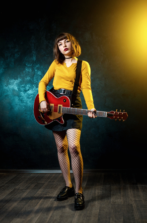 Pretty young hipster woman with curly hair with red guitar in neon lights. Rock musician is playing electrical guitar. 90s style concept.