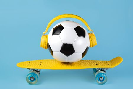 Yellow headphones on the traditional style soccer ball over blue background. Music concept.