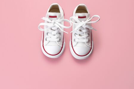 Photo of white sneakers over pink background. Top view.