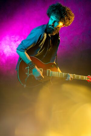 Young hipster man with curly hair with red guitar in neon lights. Rock musician is playing electrical guitar. Stock Photo - 129626349