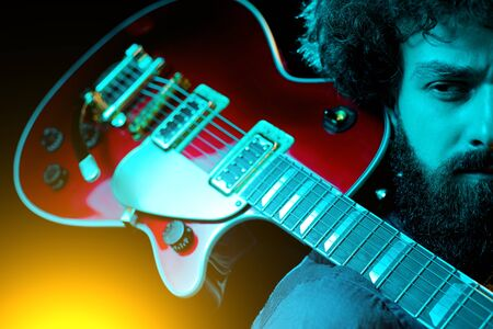 Close-up photo of hipster man with red guitar in neon lights. Rock musician is playing electrical guitar. Stock Photo