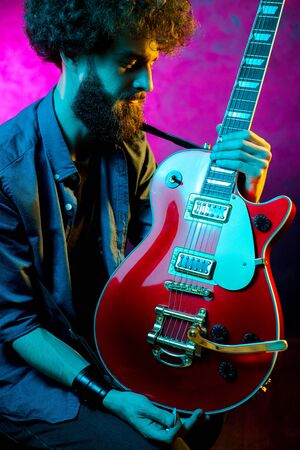 Young hipster man with curly hair with red guitar in neon lights. Rock musician is playing electrical guitar.