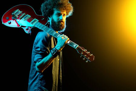 Portrait of hipster man with curly hair with red guitar in neon lights. Stock Photo