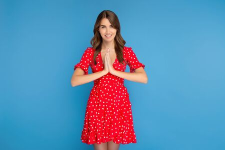 Pretty young woman with bright smile in red dress smiling while meditating against blue background.