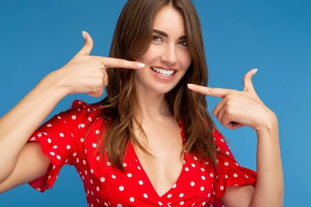 Beautiful young woman with bright smile in red casual dress looking to camera showing her white teeth over blue background.