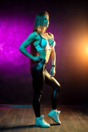 Attractive young woman fitness model posing in the studio in neon lights.