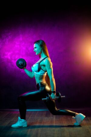 Motivated young woman fitness model workout with professional dumbbells in neon lights in the studio.