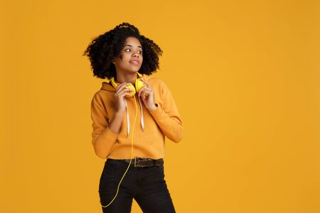 Charming african american young woman dressed in casual clothes and headphones looking away over yellow background. Archivio Fotografico - 130818401