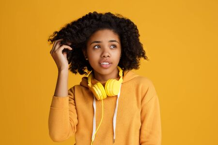 Charming african american young woman dressed in casual clothes and headphones looking up over yellow background.