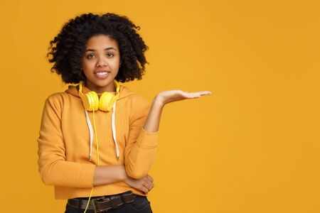 Handsome african american young woman with bright smile dressed in casual clothes and headphones clothing showing copyspace or something over yellow background.