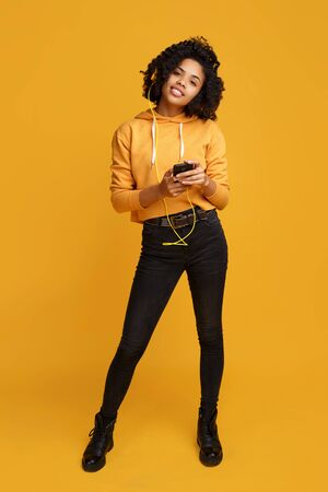 Attractive african american young woman with bright smile dressed in casual clothes with smartphone and headphones listening music over yellow background. Archivio Fotografico - 130818407