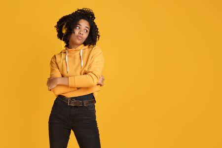 Attractive african american young woman with serious face dressed in casual clothes with smartphone and headphones listening music over yellow background.