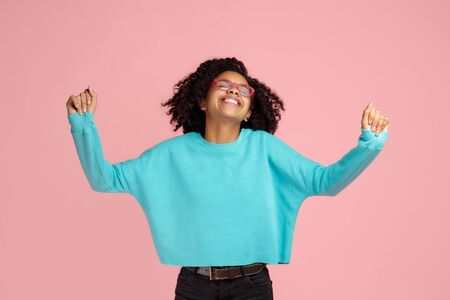 Photo of excited screaming african american young woman standing over pink background. Reklamní fotografie