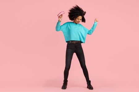 Full lengh photo of excited african american young woman with bright smile dressed in casual clothes, glasses and headphones dance over pink background.