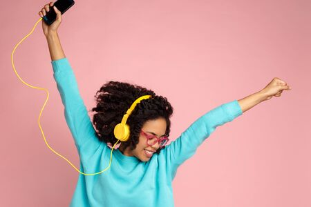Pretty african american young woman with bright smile dressed in casual clothes, glasses and headphones dance over pink background with hands up. Archivio Fotografico - 130818441