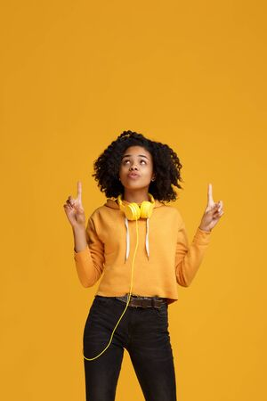 Charming african american young woman with bright smile dressed in casual clothes and headphones clothing pointing fingers up over yellow background. Standard-Bild - 130818442