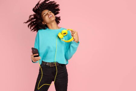 Charming african american young woman with bright smile dressed in casual clothes with smartphone and headphones dance over pink background. Фото со стока