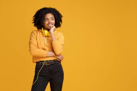 Serious african american young woman dressed in casual clothes and headphones looking away over yellow background. Standard-Bild - 130818447