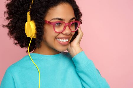 Beautiful african american young woman with bright smile dressed in casual clothes, glasses and headphones over pink background.