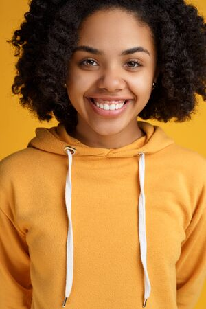 Portrait of attractive african american young woman with beautiful smile dressed in casual clothes over yellow background. Reklamní fotografie