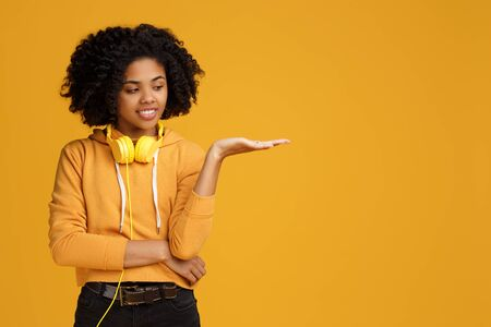 Handsome african american young woman with bright smile dressed in casual clothes and headphones clothing showing copyspace or something over yellow background. Standard-Bild - 130818454