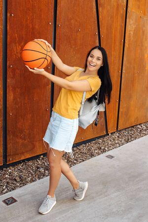 Happy brunette young woman student with bright smile dressed in casual modern clothes posing with basket ball and stylish backpack in front of rusty wall.
