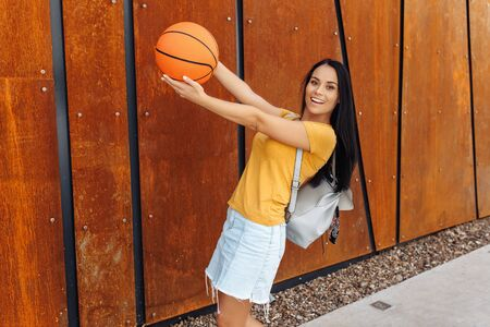 Beautiful brunette young woman student with bright smile dressed in casual modern clothes posing with basket ball and stylish backpack in front of rusty wall. Reklamní fotografie