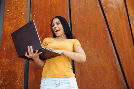 Shocked brunette young woman student with bright smile dressed in casual clothes use laptop or notebook in front of rusty wall. Фото со стока