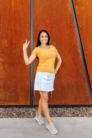 Happy brunette young woman with bright smile dressed in casual clothes showing peace gesture in front of rusty wall.