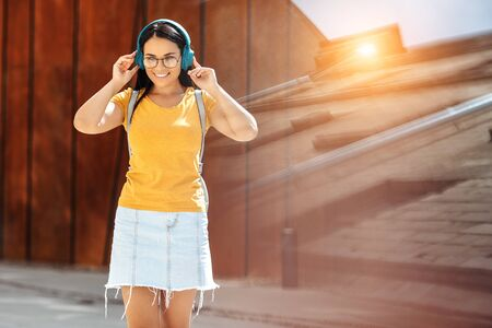 Happy brunette young woman with bright smile dressed in casual clothes listening to music with headphones and smiling. Stockfoto