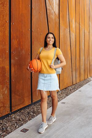 Pretty brunette young woman student with bright smile dressed in casual modern clothes posing with basket ball and stylish backpack in front of rusty wall.
