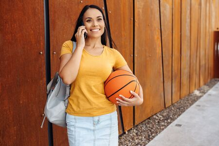 Funny brunette young woman with bright smile dressed in casual clothes holding basket ball in one hand talking on smartphone in front of rusty wall. Stockfoto