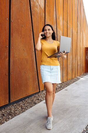 Attractive brunette young woman student with bright smile dressed in casual clothes use laptop or notebook and talking on smartphone in front of rusty wall. Фото со стока - 130818522