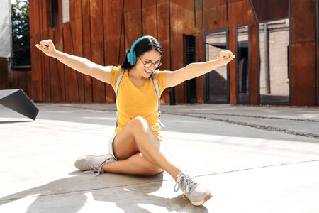Happy young woman student with bright smile dressed in casual clothes listening music on headphones while sitting on cement floor in front of rusty wall.