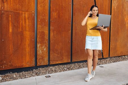 Attractive brunette young woman student with bright smile dressed in casual clothes use laptop or notebook and talking on smartphone in front of rusty wall.