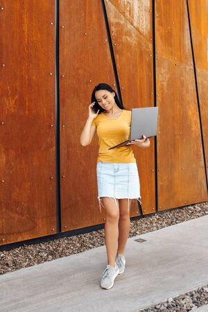 Brunette young woman student with bright smile dressed in casual clothes use laptop or notebook and talking on smartphone in front of rusty wall.