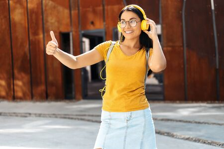 Brunette young woman student with bright smile dressed in casual clothes listening to music with yellow headphones and showing ok gesture in the street. Stockfoto