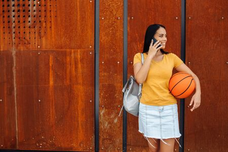 Beautiful brunette young woman student with bright smile dressed in casual clothes talk on smartphone in front of rusty wall.