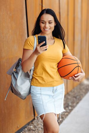 Funny brunette young woman student with bright smile dressed in casual clothes use smartphone in front of rusty wall.