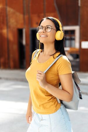 Charming brunette young woman student with bright smile dressed in casual clothes listening to music with yellow headphones and smiling in the street.