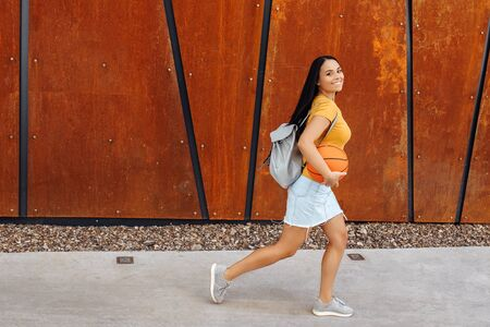 Brunette young woman student with bright smile dressed in casual modern clothes posing with basket ball and stylish backpack walking in front of rusty wall.