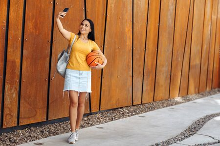 Funny brunette young woman with bright smile dressed in casual clothes doing selfie on smartphone and show ok gesture in front of rusty wall.