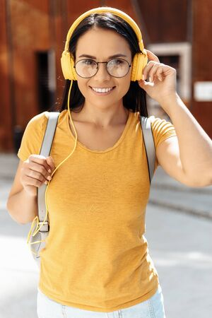 Pretty brunette young woman student with bright smile dressed in casual clothes listening to music with yellow headphones and smiling in the street.