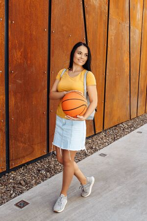 Brunette young woman student with bright smile dressed in casual modern clothes posing with basket ball and stylish backpack in front of rusty wall.