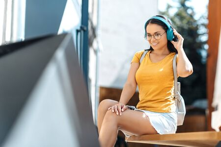 Charming brunette young woman with bright smile dressed in casual clothes listening to music with headphones and smiling.
