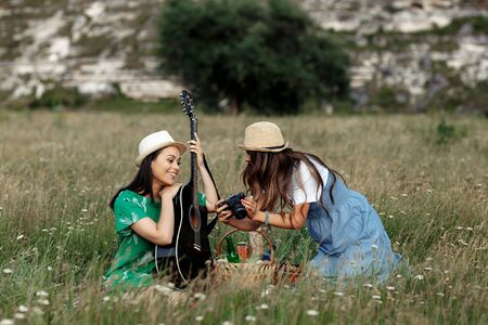 Two attractive young women sitting down on the picnic blanket and have fun with guitar and photo camera. Music and freedom concept. Stockfoto