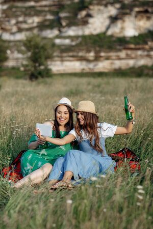 Two attractive young women sitting down on the picnic blanket and take selfie on smartphone or tablet. Beer and sandwiches. Stockfoto