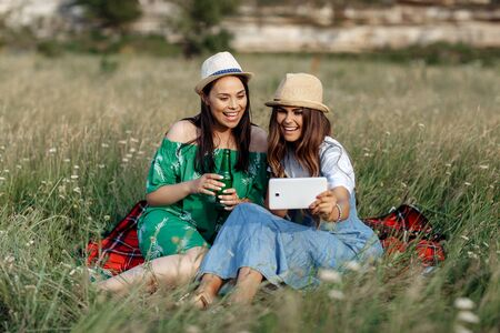 Two pretty young women sitting down on the picnic blanket and use smartphone or tablet. Beer and sandwiches.