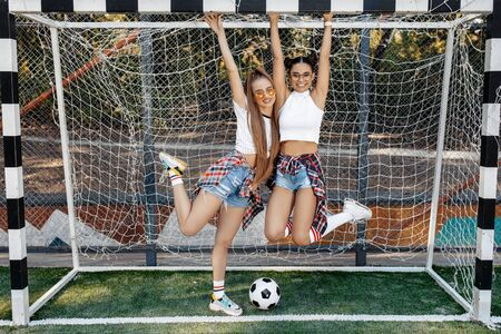 Two carefree young teenage hipster girls posing with happy faces in front of goal post at the soccer stadium. Freedom and Best Friends concept. Zdjęcie Seryjne