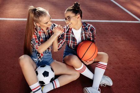 Two attractive young teenage hipster girls posing with happy faces at the stadium. Freedom and Best Friends concept. 版權商用圖片